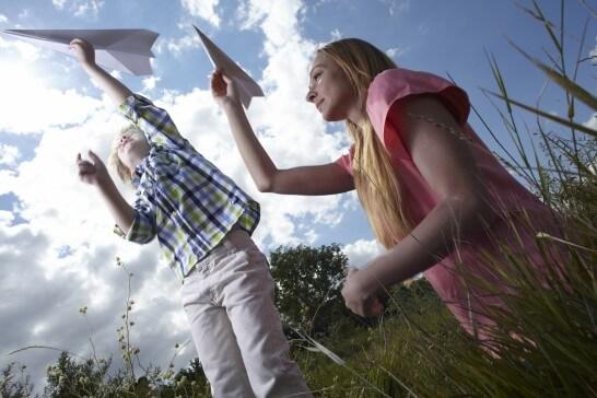 紙飛行機を投げる親子