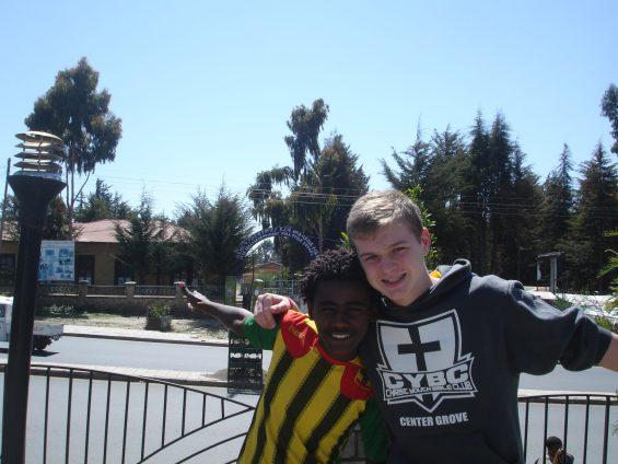 Aiden and Weldu posing in front of a school