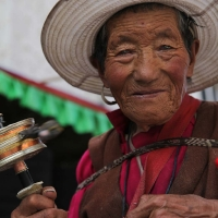 Tibetan old woman with prayer wheel