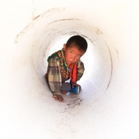 Little Tibetan boy in sewer tube