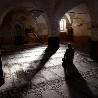 Man alone mosque with his shadow