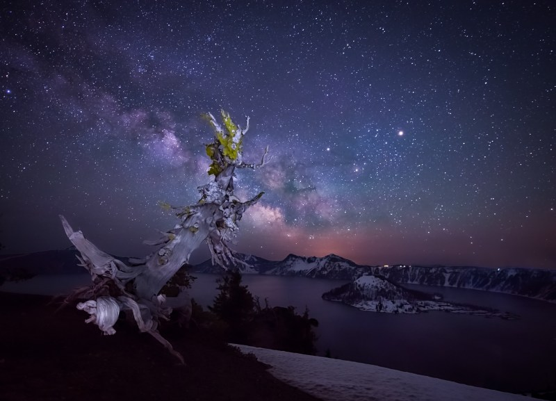 The Milky Way over Crater Lake National Park, Oregon Standing 1,000 feet above the deepest lake in the United States with 40 mph winds ripping through at midnight was one of the most thrilling photographic experiences of my life. With snow still on the ground in late May, it was about 20* when we snapped these photos at the frozen rim. We patiently waited for the Milky Way to rise over Wizard Island while attempting to keep our focus as we navigated our way through the ice and darkness. My body was violently shaking from the cold, but this place filled me with a child like joy as it is sometimes hard to comprehend the beauty of what I am seeing. Watching stars rise over a 1,996 foot deep lake was one of those moments that will be forever engrained into my mind.