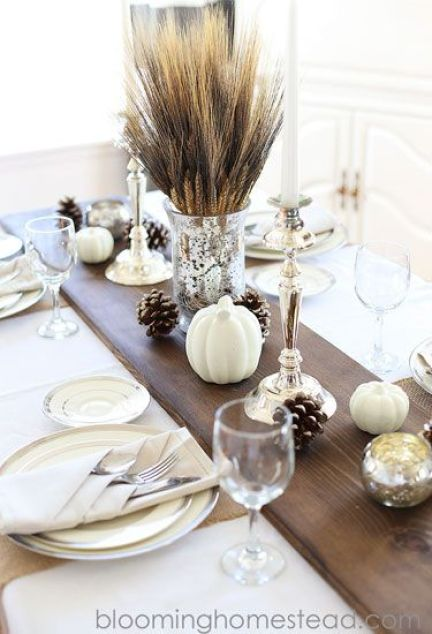 Metallic candle holders, frosted pinecones, and white pumpkins stand out against a dark stained wood table runner.