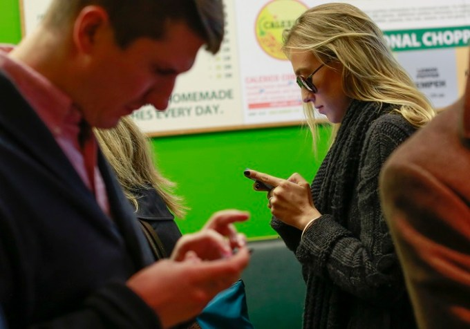 New Yorkers use their smartphones in Manhattan. Soon, they will be able to unlock their smartphones legally, and choose whatever carrier they please. [Reuters]