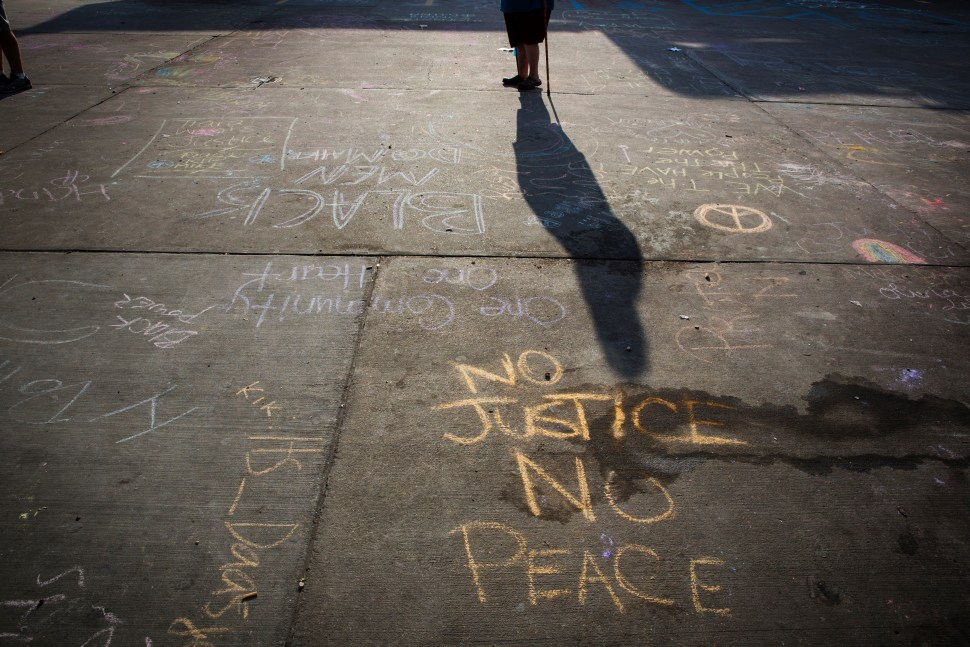 A man with a walking stick passes protest messages written in a parking lot before the announcement of the name of the officer involved in the shooting of Michael Brown in Ferguson