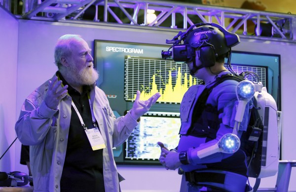 Bran Ferren (L), founder of Applied Minds, talks to a journalist dressed in an R70i aging suit. REUTERS