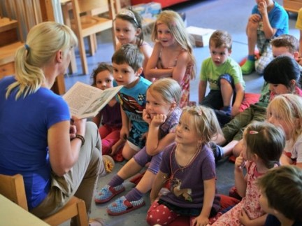 PFUNGSTADT, GERMANY - JULY 11: Kindergarten teacher Jennifer Karbot reads a fairy tale about ghosts to her children in a Kindergarten (Kita) on July 11, 2013 in Pfungstadt, Germany. According to numbers which were published by German Family minister Kristina Schroeder, the country reached a family-friendly milestone in boosting the …
