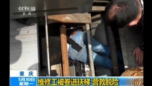 Rescuers work to free repariman in China after he is pulled into machinery of escalator