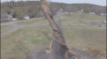 Smokestack demolition gone wrong, falls on top of backhoe, driver unharmed