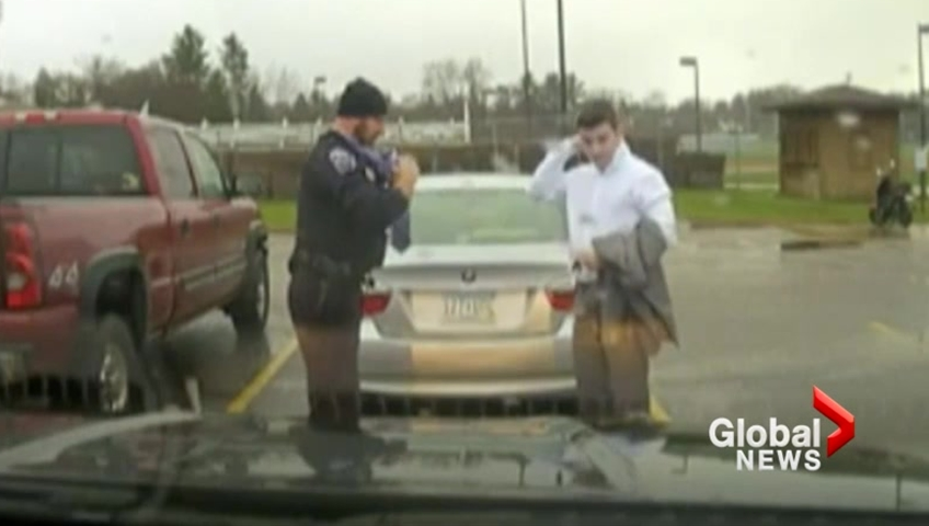 Officer helps tardy student tie his tie during traffic stop