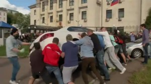 Ukrainian protesters flip cars in front of Russian Embassy