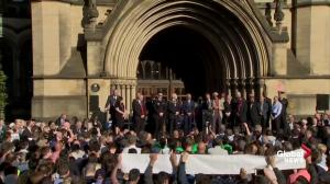 Arms raised in defiance, Manchester residents hold moment of silence