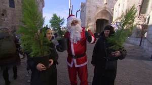 Santa gives out Christmas trees in Jerusalem's old city