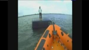 Rescuers retrieve man standing atop his van (in the ocean)