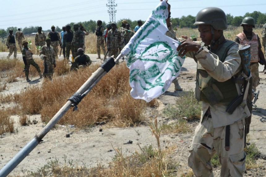 FILE PHOTO: A Nigerian soldier pull down a Boko Haram flag as a mark of victory