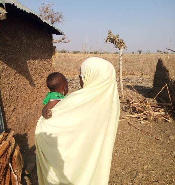 Zara John, 16, holds her baby, with her mother watching in the background. TRF/Mohammed Umaru