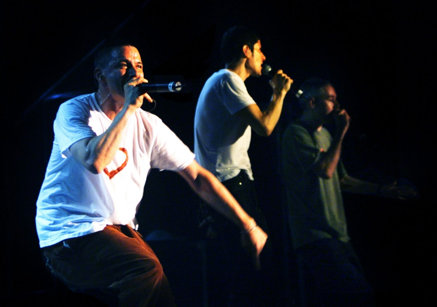 Three men hold microphones and perform on a stage