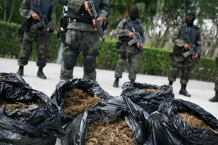 Soldiers stand guard next to bags of marijuana being displayed to the media at a military base on the outskirts of Monterrey, Mexico.