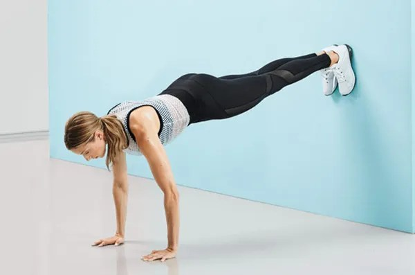 Works: arms, chest, back, core, quads Kneel with back to wall, hands on floor slightly wider than shoulder-width apart. One at a time, place feet on wall slightly higher than shoulders (as shown). Hold for 30 seconds, then do push-ups for 30 seconds, keeping arms close to body. (Make it easier: Place feet on floor.)