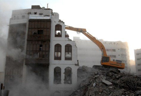 Image of It is an endless debate whether and how much traditional neighborhoods with their traditional landmarks should give way to colossal Holy Mosque development and expansion programs. An excavator in action tearing down a Shamiyyah building