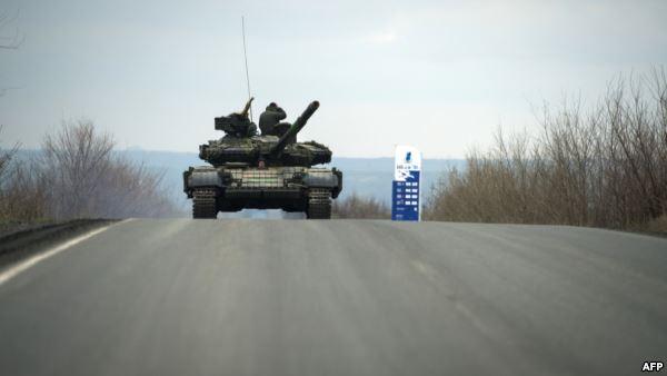 Pro-ruskí separatistickí vojaci stoja na svojom tanku počas jazdy na ceste do obci Kirovsk 21.4.2015 v samozvanejj Doneckej ľudovej republike (DNR).