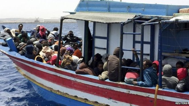 Migranti, ktorí sa pokúsili plávať do Európy sedia v lodi idúcej naspäť do Líbye, potom, čo ich loď bola zadržaná na mori líbyjskou pobrežnou strážou, v Khoms, Líbya, 06.05.2015