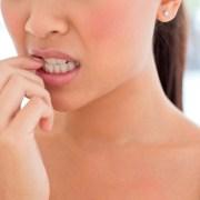 Young woman biting nails.