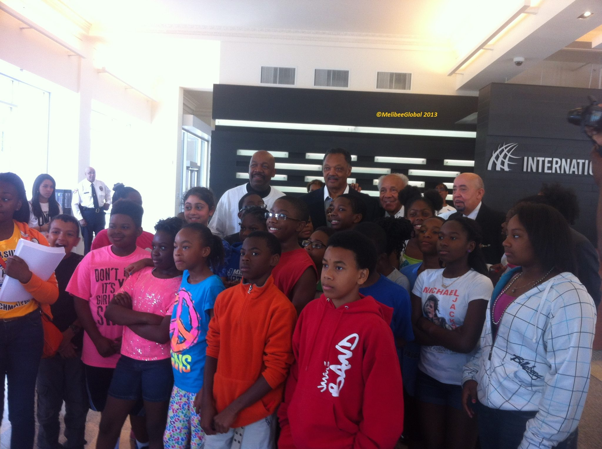 Reverend Jackson spoke with a group of students while the press encouraged a group photo.