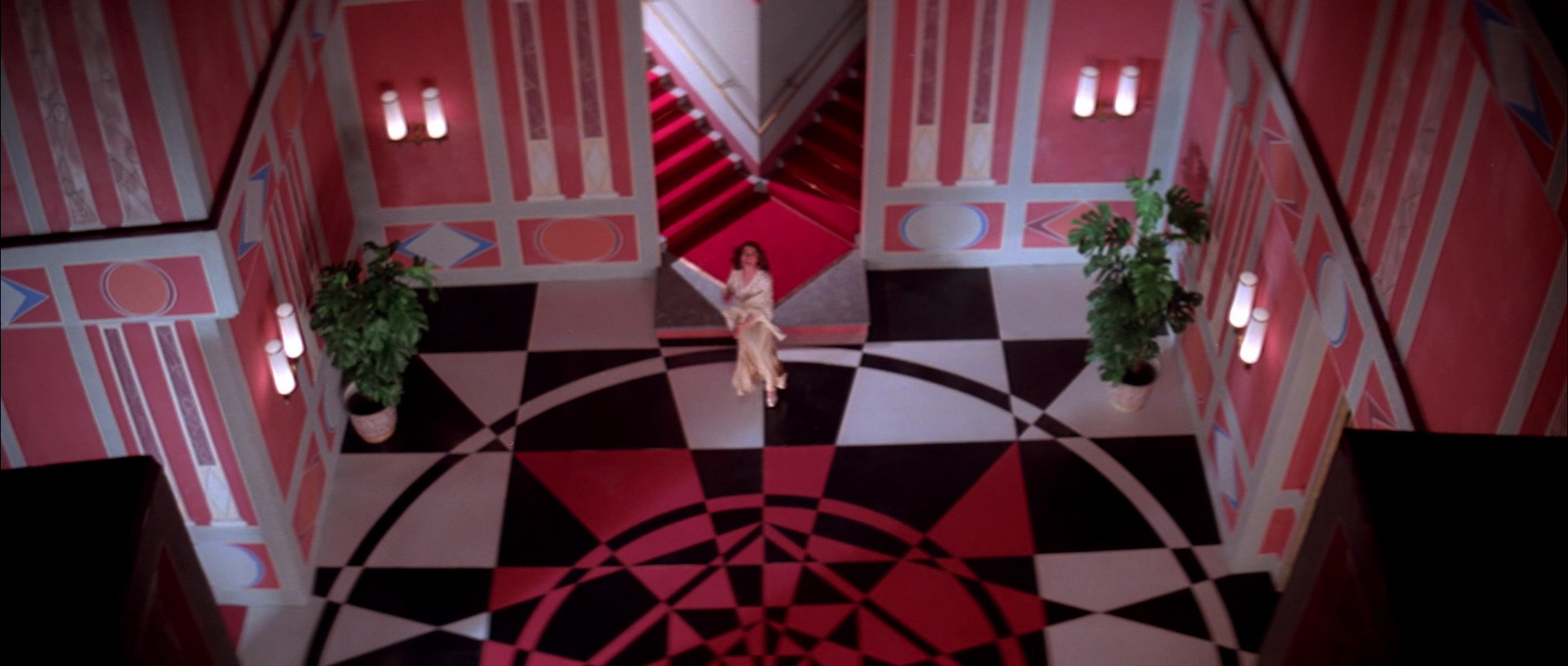 High-angle shot of a white, black and red room with a striking abstract mural on the ground. A person with white skin and long brown hair wearing a pink dressing gown appears to be running into the room from a forked stairway.