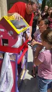 Dad Van Morris holds the ribbon for daughter Kara to open the Little Library. Photo courtesy of Kathy Morris
