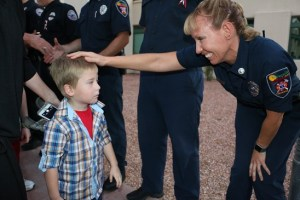 A local child too young to remember the tragedy is greeted by Karen Hughes, left, a Mesquite firefighter at the city's September 11 commemoration ceremony. Photo by Barbara Ellestad.