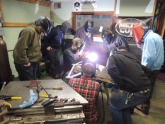 Students look on as Frank welds drop outs