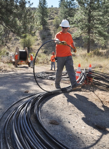 Jeff Stevie and the rest of the crew from Maxwell Communications spread cable to be installed near Benson Creek. Photo by Sue Misao