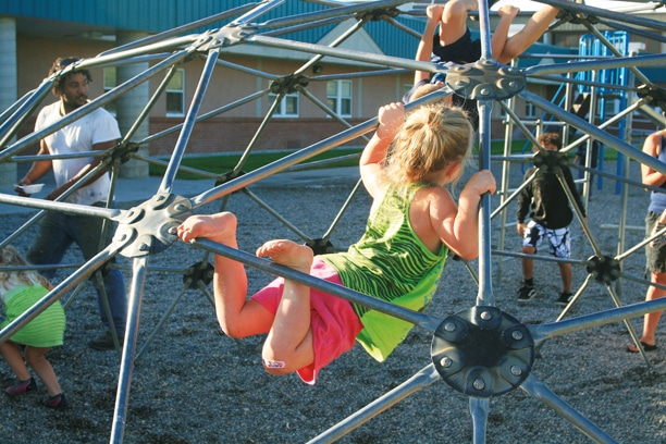 Meanwhile, five days earlier, students and their families were invited to an ice cream social at the elementary school, where they met other families, school district staff, and enjoyed the playground. Here, Clara George gives the jungle gym a workout. Photo by Marcy Stamper