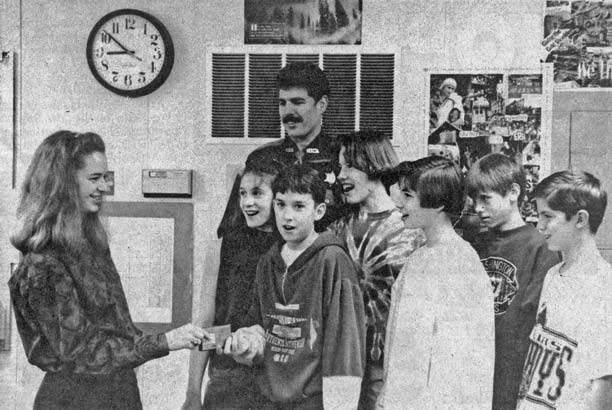 DRUG BATTLERS. Seventh graders, left to right Jocelyn Coe, Cory Loucks, Erin Torpey, Misty Gage, Ryan Ellis and Cameron Erkela, accompanied by deputy Kevin Murray, handed Dawn Eliassen of Liberty Bell Live, their D.A.R.E. public service announcements which will be played on the KVLR show. The recordings, made as an addition to the regular D.A.R.E. curriculum, can be heard at 15 and 45 past the hour during the student-run Monday 7 p.m. to 9 p.m. slot.