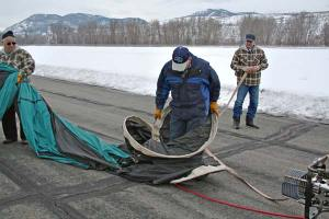 "Pilot Steve Justice does the ""hoop dance"" that will maneuver the ring  back into a size that will fit inside the carrying bag. Brother Steve Justice, 2nd crew chief, looks on. Photo by Darla Hussey"