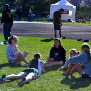 Liberty Bell track ladies stretch and rest on the infield. Photo by Laurelle Walsh