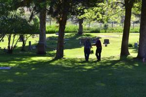Claude Miller and Duffy Dufresne walk down the tree-lined central aisle of Sullivan Cemetery.Photo by Laurelle Walsh