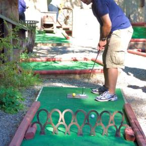 Clubs for the Booster Club. Firefighters from Okanogan County Fire District 6 held off the other five teams that competed in the Liberty Bell Booster Club's third annual Mountain Lion Mini Golf Tournament held at Sherri's Sweet Shoppe on Sunday (Sept. 14) to successfully defend their 2013 title. The fire district team of Brian McAuliffe (above), Bill McAdow, Mark Crum and Zach Gurney had a score of 98, enough the claim the 2014 trophy along with a half-pound of fudge for each team member. Second place went to Winthrop Kiwanis, third to Team Divot from Aero Methow Rescue, fourth to Team Haley, and fifth to the Aero Methow Odd Balls. The tournament is a fundraiser for the Liberty Bell Booster Club to assist with, and support, school activities programs at the high school. Equipment, facilities, uniforms and pay-to-play assistance are just some of the things the club supports. Photo by Ashley Lodato