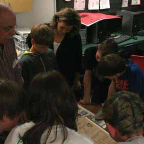 The fifth and sixth graders enjoyed looking at old newspapers from 100 years ago. Photo by Darla Hussey