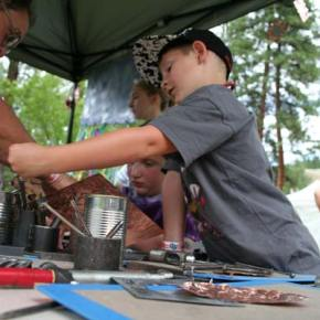 Local artist Barry Stromberg help kids make embossed copper mirrors. Photo by Darla Hussey