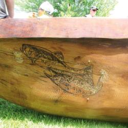 A symbolic salmon etched into the side of the canoe.