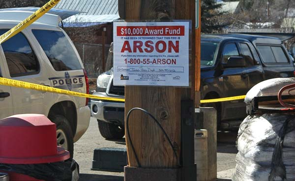 Photo by Ann McCreary A sign posted in front of the Twisp River Pub offers a reward for information about the fire, which investigators have determined is arson.