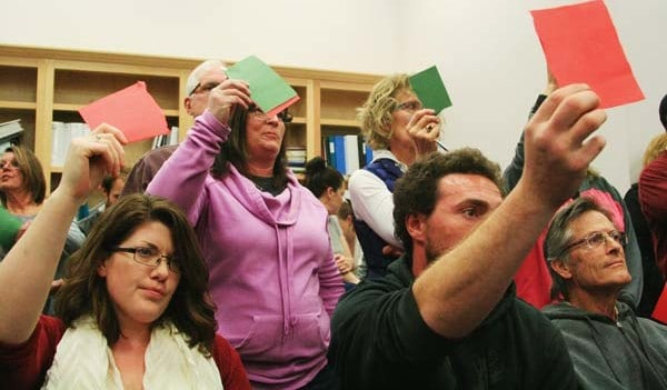 Photo by Marcy Stamper Attendees at the zoning hearing held up red and green cards — distributed by those who want the county to continue to treat marijuana like any other crop — to signal their support or opposition as speakers addressed the county planning commission.