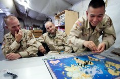 Sgt. James Jackson, left, tries to hide a smile as Lt. Travis Loustaunau watches Spc. Phokhan Kamlue attack the lieutenant's position during a game of Risk in the Moral, Welfare and Recreation tent in Uzbekistan, 2003. The soldiers, serving in the Forward Supply Battalion of the 10th Mountain Division from Fort Drum, were waiting to fly into Afghanistan after their initial flight developed engine trouble over the Hindu Kush mountains. - The Watertown Daily Times