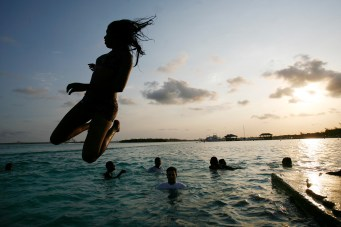 A Dominican teenager jumps off of a concrete pier into the Caribbean Sea as friends watch and swim at the Boca Chica Beach at sunset.