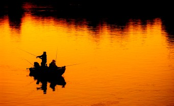 Two fishermen cast their lines into the mouth of the Black River in Dexter as the sun sets. - The Watertown Daily Times