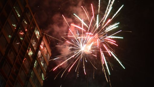 Firecrackers exploding in dark sky near building