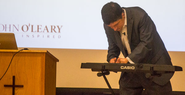 Although his fingers were amputated after fire burned 100 percent of his body, author John O'Leary showed students at Cristo Rey High School he can still play the piano – a message that it is possible to overcome even great difficulties in life.