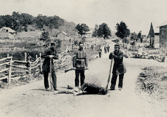 Canadian troops pose with the body of a dead Fenian, 1870.